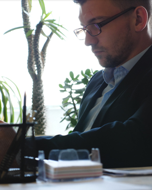 A man wearing eyeglasses, working at a desk.