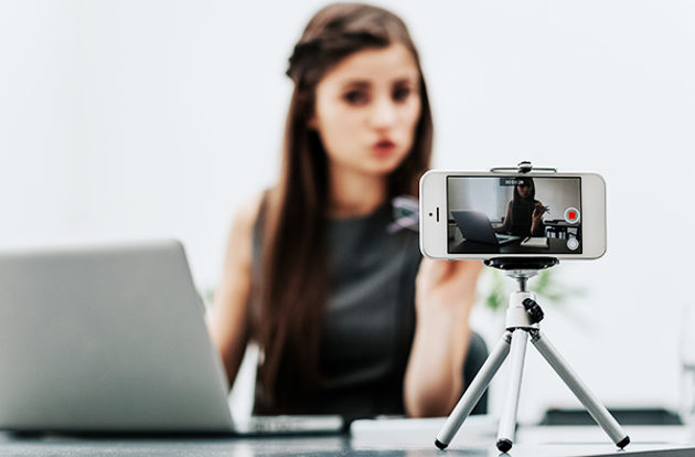A woman filming with a smartphone mounted on a mini tripod.