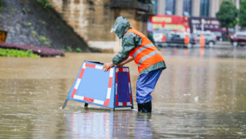 A worker putting equipment out in flooded streets.