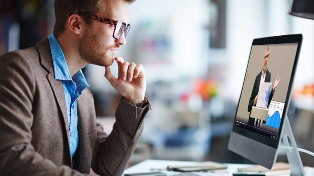 A man wearing eye glasses watching a video on a desktop computer.