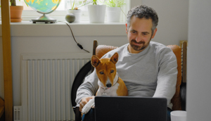 A man working on his laptop with a dog sitting on his lap.