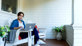 A woman working on a laptop on a porch.