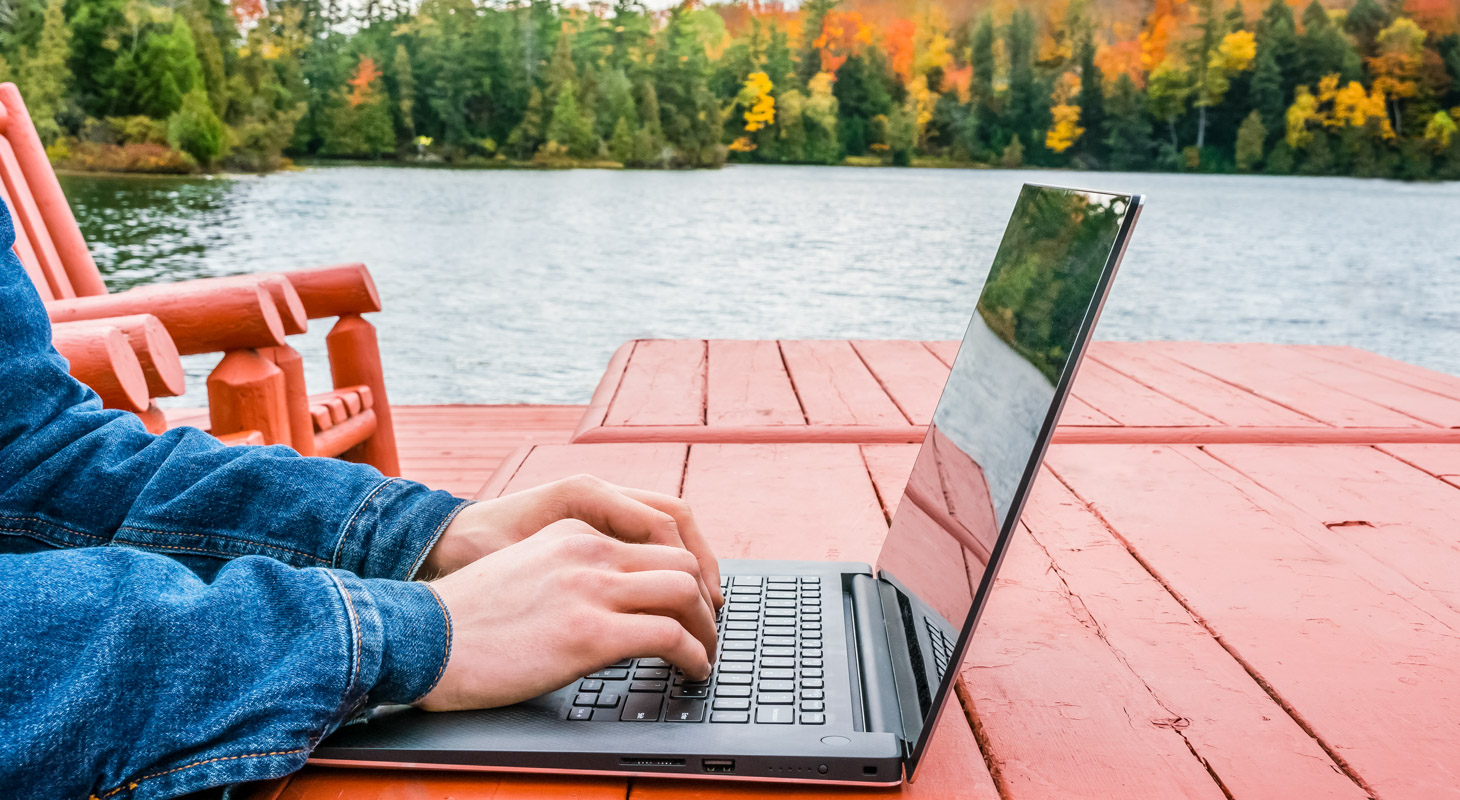 A person working on a laptop outside on a orange table with a view of a lake.