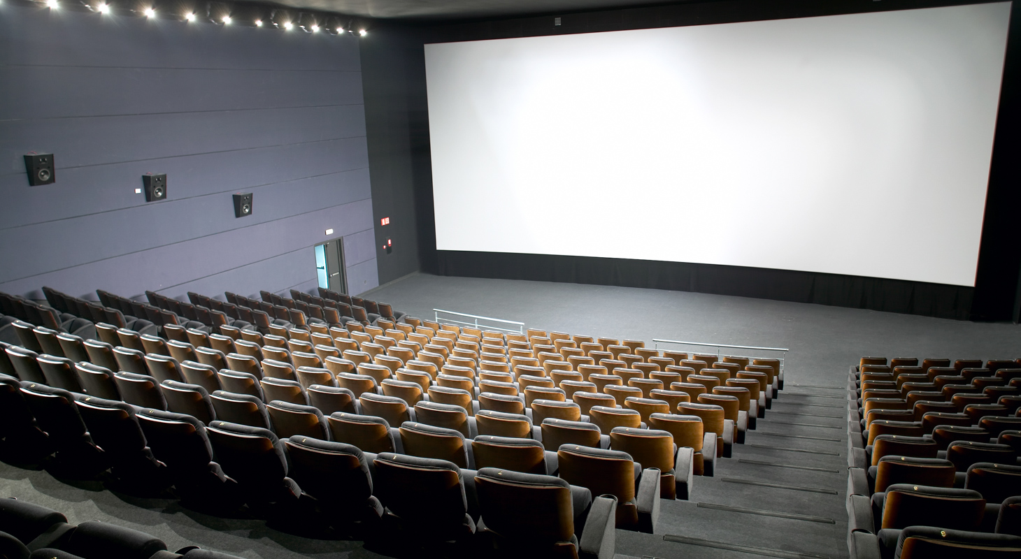 Modern cinema interior with seats and screen.