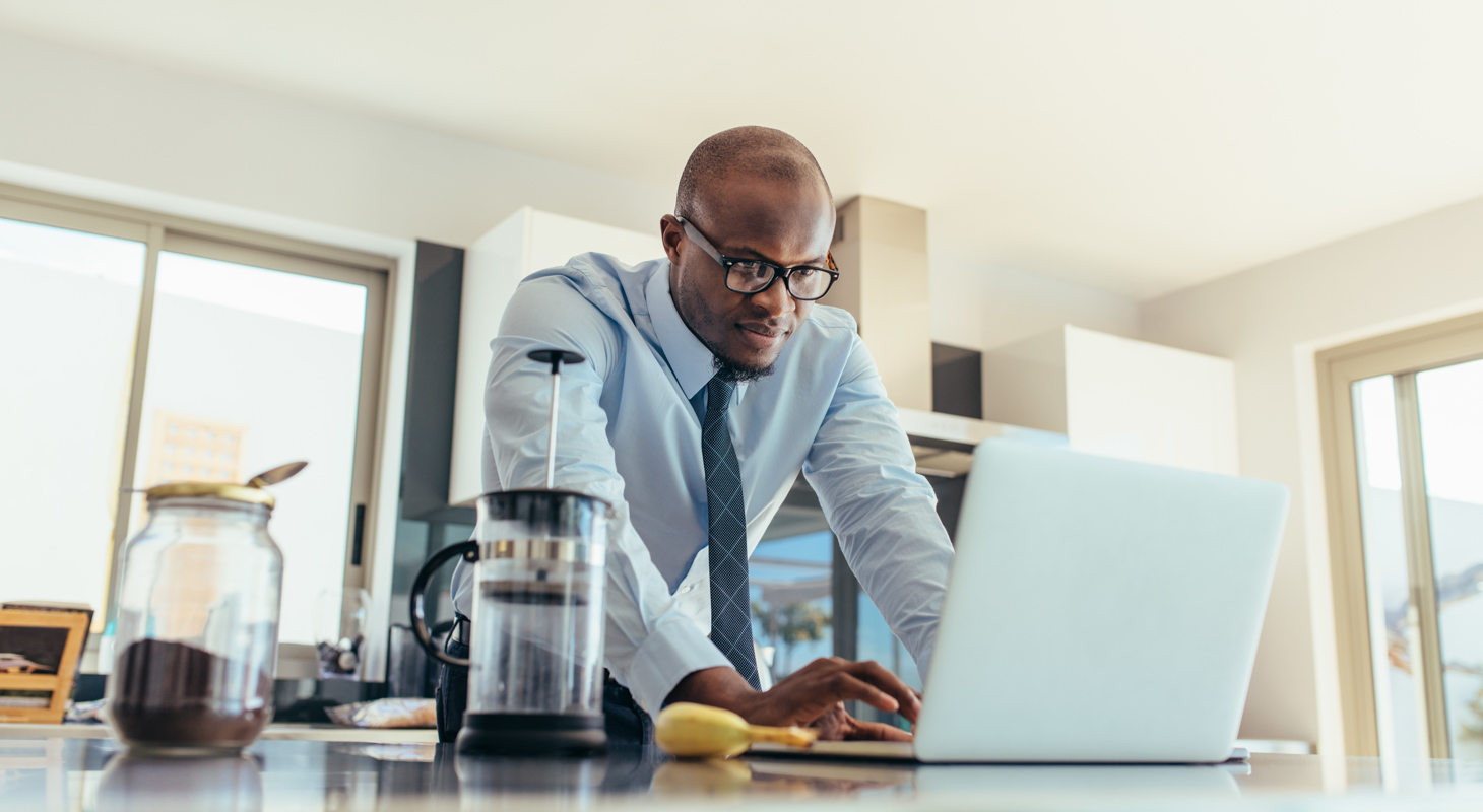 Businessman using a laptop on kitchen table at home.