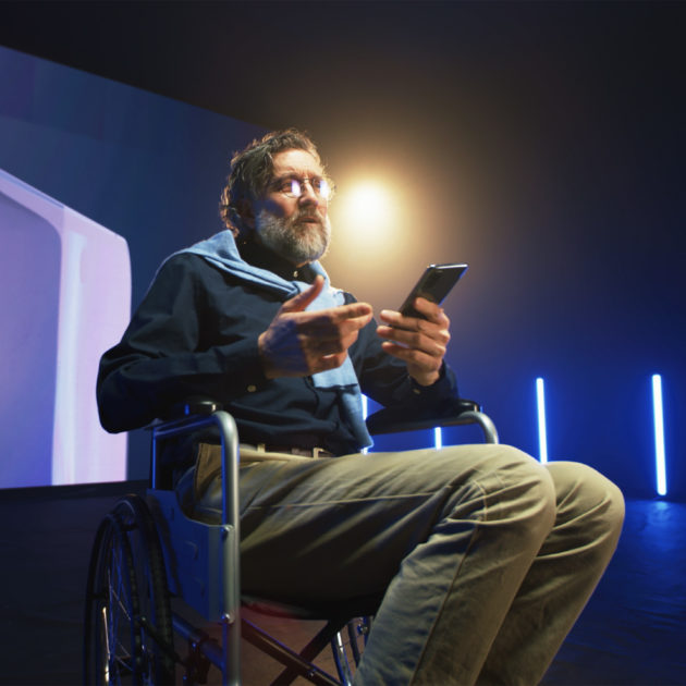 A man in a wheelchair presenting on stage.